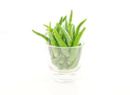 Green chili bunch in cup on white background Stock Photo
