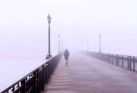 Landscape with  lonely lady crossing a bridge in the misty morning