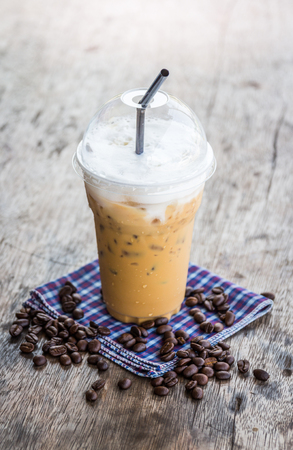 Iced Coffee on old wood desk with coffee beans