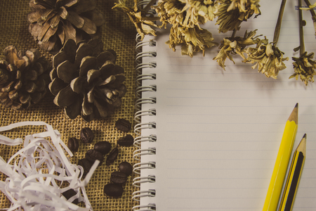 Pencil on notebook with dry flower on burlap background