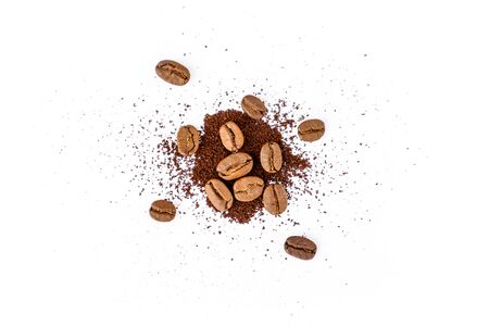 Roasted coffee beans with ground coffee on white background Фото со стока