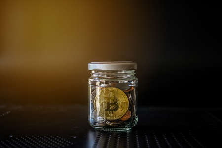 Gold bitcoin and money coin in glass jar on black background. Crypto currency and finance concept.