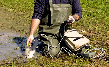 A scientist measuring environmental water quality in a wetland Stock Photo