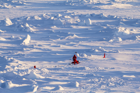 floe: Two polar scientists in red polar clothing working on ice cores over an ice floe