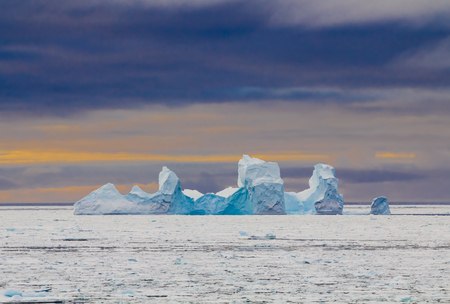 Blue colored iceberg in Antarctica Weddell Sea during sunset