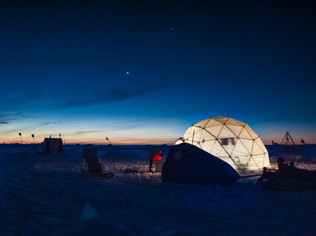 oceanography: Researcher working at an ice camp under clear polar sky