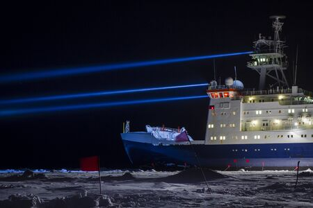 oceanography: Icebreaker research vessel near a research site marked with safety flags searching by strong projectors Stock Photo