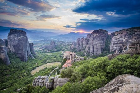 Sunset at Meteora with monastries situated above limestone rock pillars