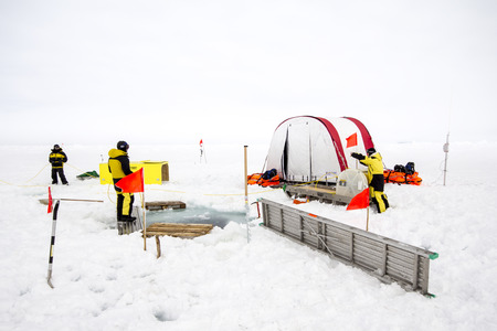 Weddell Sea, Antarctica – September 19, 2013: Scientists from a research icebreaker are establishing a remotely operated vehicle (ROV) camp over an ice floe to explore under ice algal growth