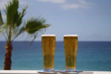 holliday: Cold glasses of beers with a seaview Stock Photo