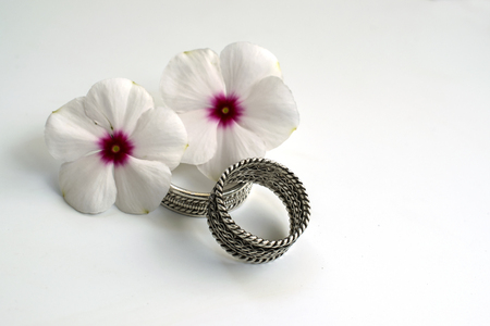 youthfulness: Wedding Rings with Flowers Two wedding rings and two flowers that symbolize the youthfulness and beauty of a young married couple.