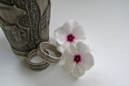youthfulness: Engraved Metal Cup with Wedding Rings and Flowers Wedding Rings with engraved metal cup and two flowers that symbolize the youthfulness and beauty of a young married couple.