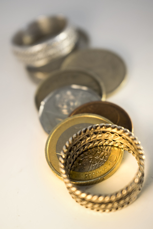 financial planning married: Marriage for Money Two wedding rings and coins that symbolize the people who get married for money and interest Stock Photo