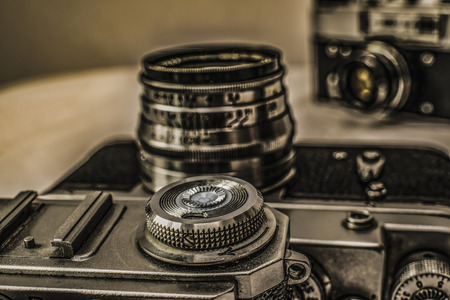 Close up view of old Russian analog film camera with vintage look. On the camera, there can be seen film rewind crank and flash hot shoe buttons. In background is another old camera with lens