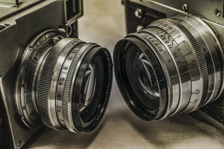 Close up view of two old Russian analog film cameras with the lenses facing each other on dirty canvas with vintage look