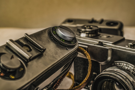 Close up view of old Russian analog film camera with vintage look. On the camera, there can be seen aperture ring, focusing ring, lens, filter thread. In background is another old camera with lens Stock Photo