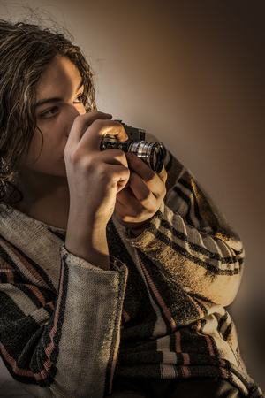 Young boy with long blond hair dressed in sweater. He holding an old russian camera in his hands, and taking a shot Stock Photo