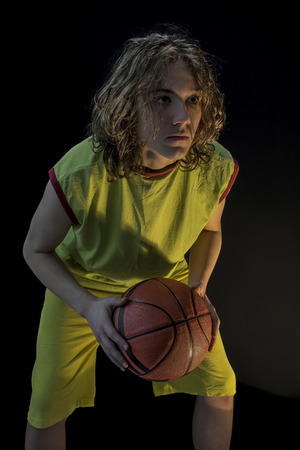 en cuclillas: Young boy with long blond hair wearing a green jersey in a squatting position and holding a basketball focusing on the making the shot.