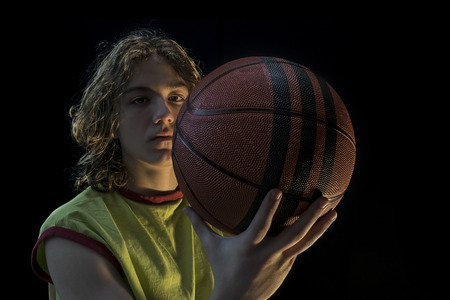 Close up view of a young boy with long blond hair wearing a green jersey holding up a basketball looking at the camera.