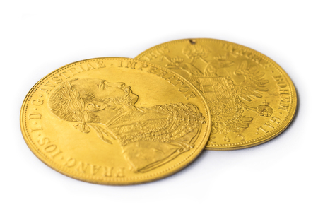 facing right: Close-up view in perspective of two on one another Austria-Hungary thalers, avers and revers of golden coin-ducats from 1915 with Kaiser Franz Joseph I, on white background