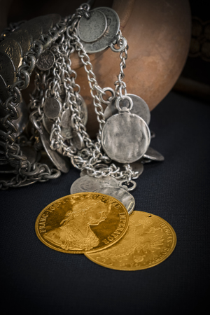 facing right: Still Life with two Austria-Hungary thalers, avers and revers of golden coin-ducats from 1915 with Kaiser Franz Joseph I, leaning on silver jewelery and dark environment Stock Photo