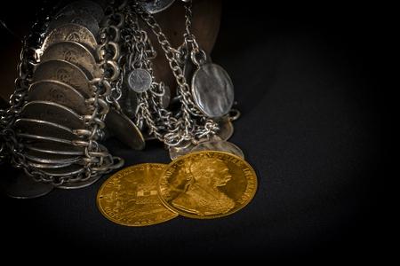 monedas antiguas: Naturaleza muerta con dos táleros de Austria-Hungría, avers y reversa de monedas de oro-ducados de 1915 con Kaiser Franz Joseph I, apoyado en joyas de plata y ambiente oscuro Foto de archivo