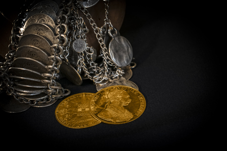 monete antiche: Still Life with two Austria-Hungary thalers, avers and revers of golden coin-ducats from 1915 with Kaiser Franz Joseph I, leaning on silver jewelery and dark environment Archivio Fotografico