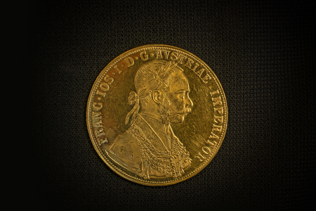 facing right: Close-up view of Austria-Hungary thaler, avers of golden coin-ducat from 1915 with Kaiser Franz Joseph I on dark background