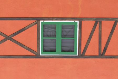 detail of a wooden window with shutters close on orange wall  photo