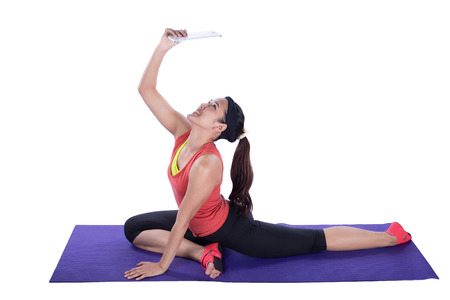 asian woman doing yoga with tablet against white background photo