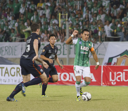buriram: PATHUMTHANI THAILAND- NOVEMBER 10:T.Winothai(green) in Thaicom Fa Cup between Buriram United(blue) vs Bangkokglass Fc(green) on November 10, 2013 at Thammasat Stadium in Pathumthani Thailand