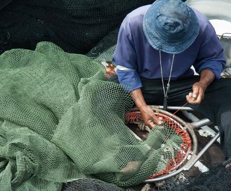 fishnet: fisherman is repairing  green fishnet