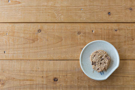 peice: a peice chocolate chip cookie on wood background and free text space