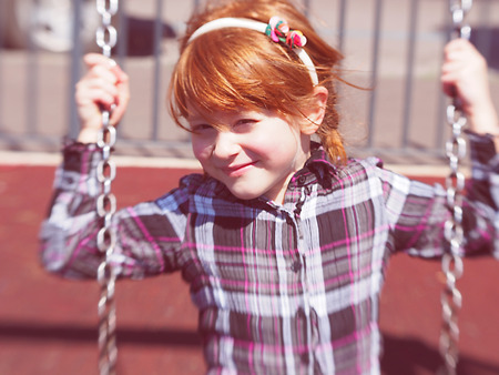 lightsome: five-year-old little girl with red hair sitting  on the swing and smiling