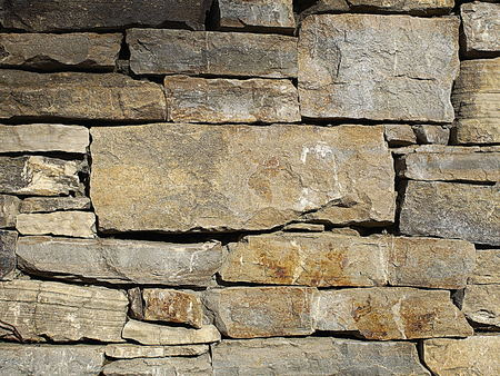 Stacked stone wall with a large stone in the midlle for text