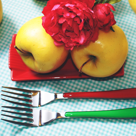 colorful still life: Colorful still life with yellow apples, red flower and colorful forks and plate on checkered table cloth Stock Photo
