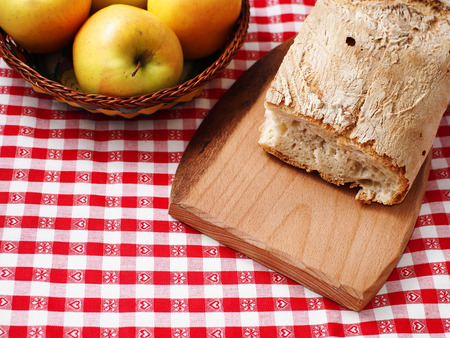 Stil: Picnic stil life with bread on wooden cutting board and apples in a basket on red checkered table cloth Stock Photo