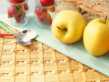 wattled: Apples and strawberries on wattled surface with checkered table cloth and bread in the background Stock Photo