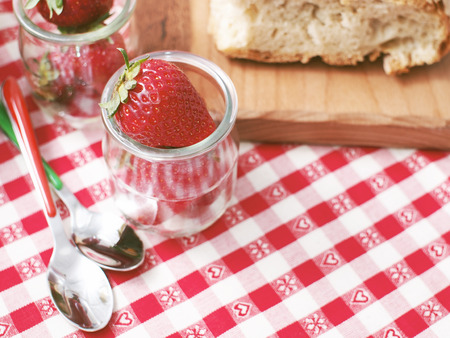 Stil: Picnic stil life with bread on wooden cutting board and strawberrie in glass cups on red checkered table cloth