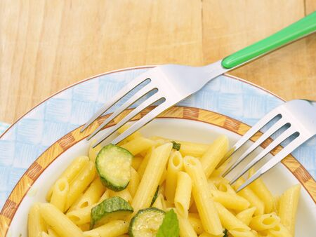 trencher: Italian short pasta penne with unpeeled zucchini and mint on wooden trencher