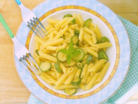 trencher: Italian short pasta penne with zucchini and mint on wooden trencher Stock Photo