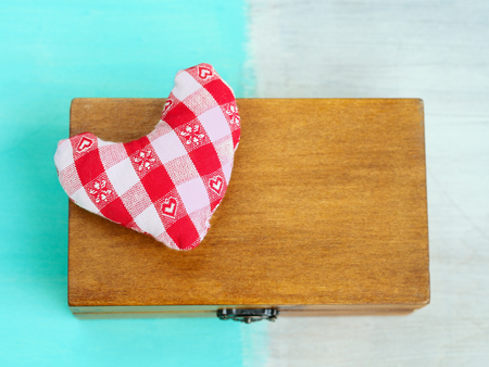 tresure: Soft checkered stuffed heart on the surface of a wooden box on mixed color wooden background Stock Photo
