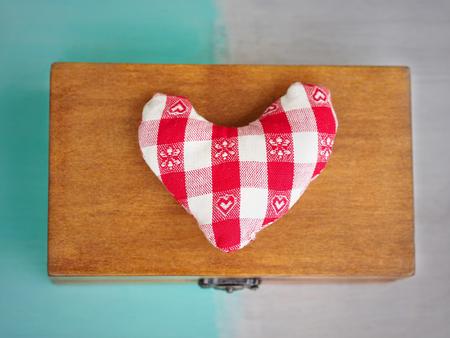tresure: Soft checkered heart on a closed wooden box Stock Photo