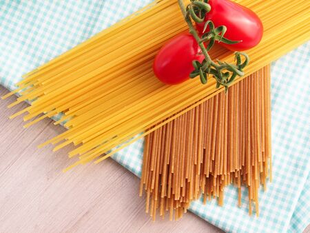 refined: Whole wheat pasta spaghetti with traditional refined wheat flour spaghetti on checkered table cloth on wooden table with two tomatoes