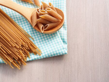 wheat: Whole wheat pasta - spaghetti and short pasta penne in wooden spoon on checkered table cloth on wooden table, copy space Stock Photo