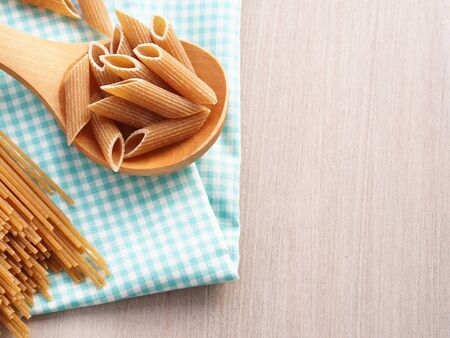 short pasta: Whole wheat pasta - spaghetti and short pasta penne in wooden spoon on checkered table cloth on wooden table, copy space Stock Photo