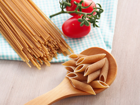 short pasta: Whole wheat pasta - spaghetti and short pasta penne in wooden spoon on checkered table cloth on wooden table