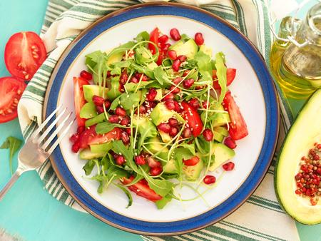 aguacate: Ensalada vegetariana con aguacate, rebanadas de tomate, hojas de r�cula, la granada y las semillas de s�samo Foto de archivo