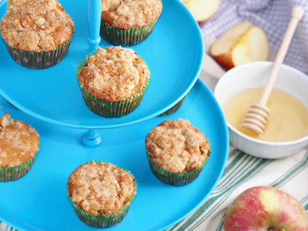 crumb: Apple crumb spiced muffins on blue muffin stand with table napkins, apples and a bowl with honey in the background Stock Photo