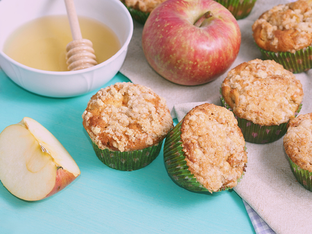 crumb: Apple crumb spiced muffins on on green pastel wooden table with table napkins and an apple